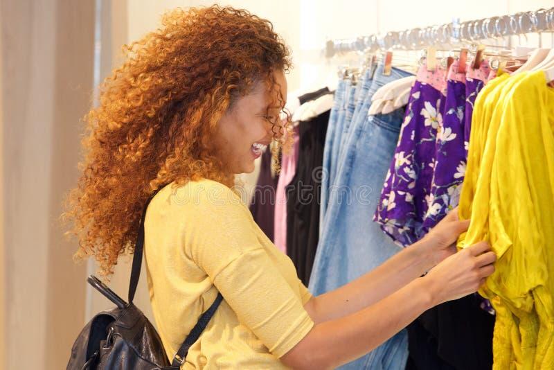 Glückliches Einkaufen der jungen Frau für Kleidung im Speicher lizenzfreie stockbilder