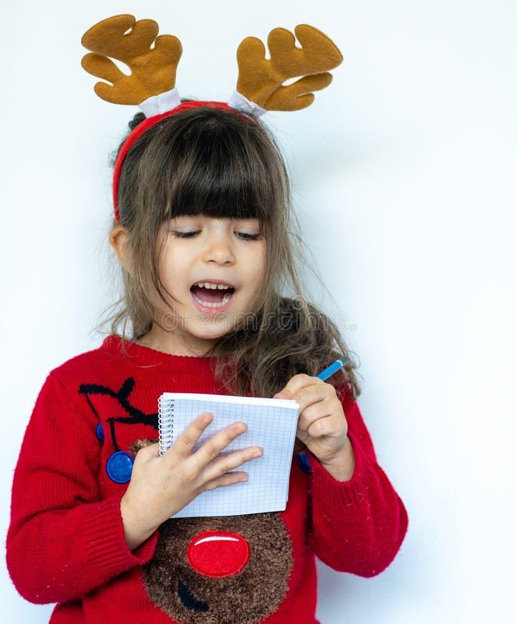 Glückliches Einkaufenmädchen auf weißem Hintergrund Schöner entsetzter Kinderbehälter und eine Einkaufsliste für Verkäufe des neu lizenzfreies stockfoto