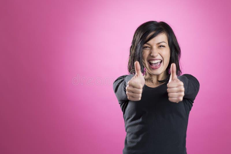 Glückliches enthusiastisches Mädchen, das Daumen aufgibt stockfoto