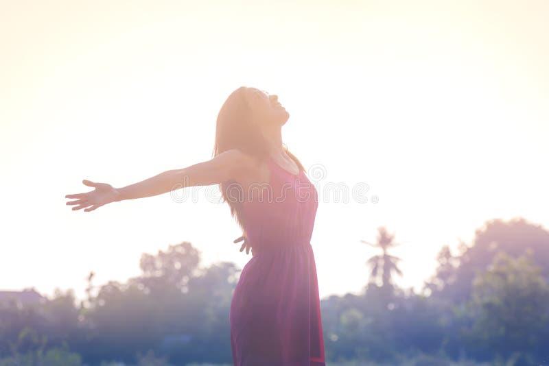 Glückliches entspannendes Lächeln der jungen Schönheitsfrau im Sommersonnenunterganghimmel heraus lizenzfreie stockfotos