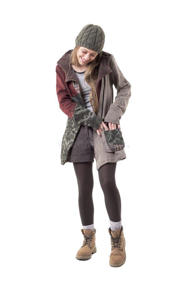 Glückliches entspanntes Hippie-Artmädchen mit dem Beanie, der nach etwas in der Handtasche sucht lizenzfreie stockbilder