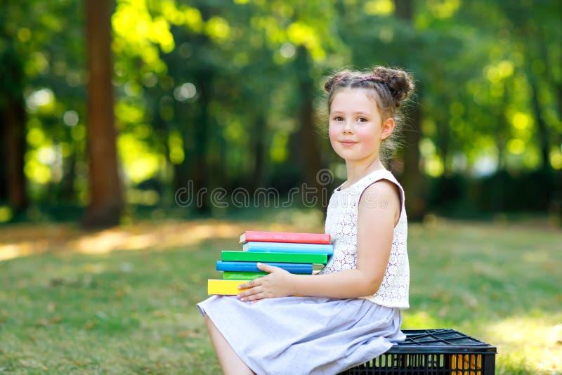 Glückliches entzückendes Kleinkindmädchen-Lesebuch und verschiedene bunte Bücher der Holding am ersten Tag zur Schule oder zur Ki stockbild