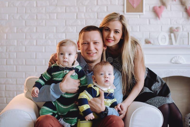Glückliches Familie portrair Eltern mit Jungenzwillingen des Babys zwei Porträt der glücklichen Familie mit zwei Kindern stockbild