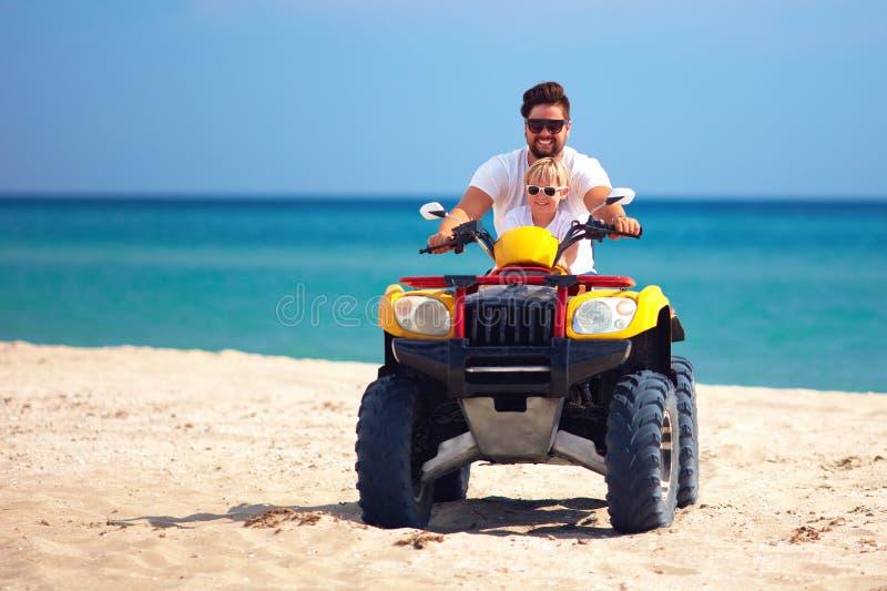 Glückliches Familien-, Vater- und Sohnreiten auf atv viererverseilen Fahrrad am sandigen Strand lizenzfreies stockfoto