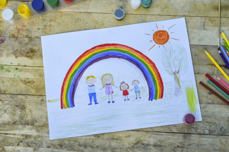 Glückliches Familienkonzept Blatt mit einem Muster auf einem Holztisch: Eltern und Kinder halten Hände gegen Hintergrund des Rege lizenzfreie stockfotografie