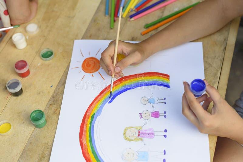 Glückliches Familienkonzept Kind zeichnet auf ein Blatt Papier: Vater-, Mutter-, Jungen- und Mädchengriffhände gegen Hintergrund  lizenzfreies stockfoto