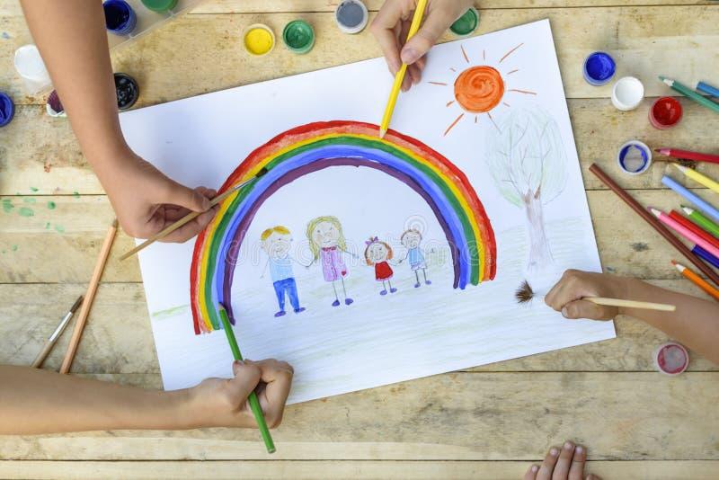 Glückliches Familienkonzept Mit-Schaffung Kinderhände zeichnen auf ein Blatt Papier: Vater-, Mutter-, Jungen- und Mädchengriffhän stockfoto