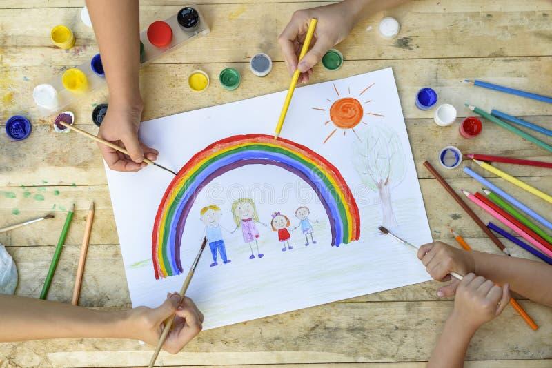 Glückliches Familienkonzept Mit-Schaffung Kinderhände zeichnen auf ein Blatt Papier: Vater-, Mutter-, Jungen- und Mädchengriffhän stockfotos