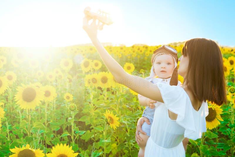 Glückliches Familienkonzept Schöne junge Mutter und Baby in den gelben Sonnenblumen auf Natur im Sommer mit hölzernem Flugzeug sp lizenzfreies stockbild