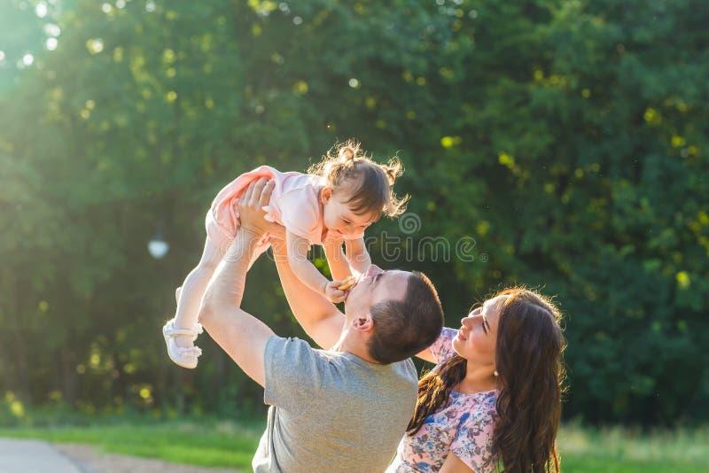 Glückliches Familienkonzept - Vater-, Mutter- und Kindertochter, die Spaß hat und in der Natur spielt stockfotografie