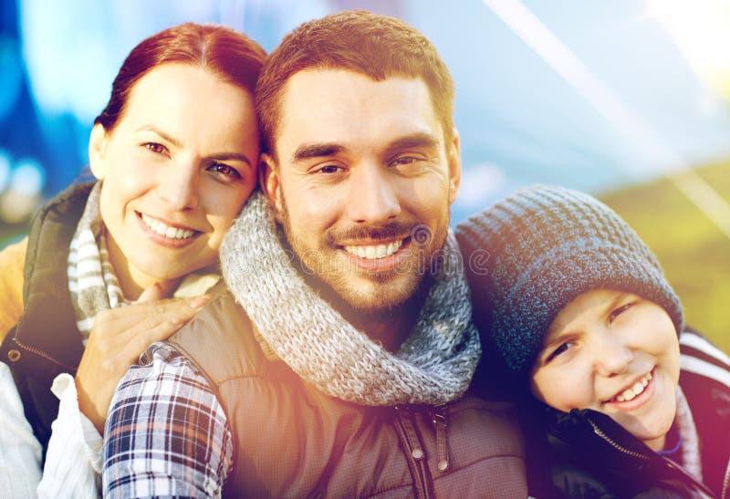 Glückliches Familienporträt über Zelt am Zeltplatz stockbild