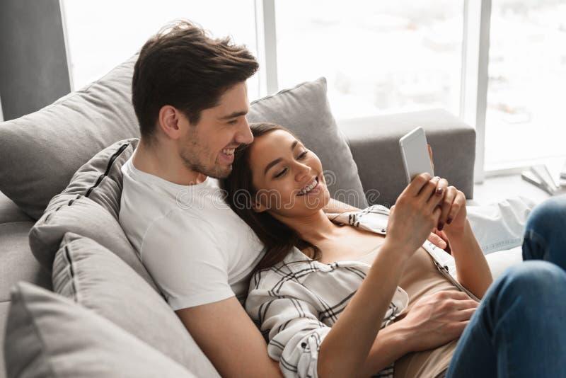 Glückliches Familienporträt des liebevollen Mannes und der Frau, die auf Sofa an h liegt lizenzfreie stockfotos