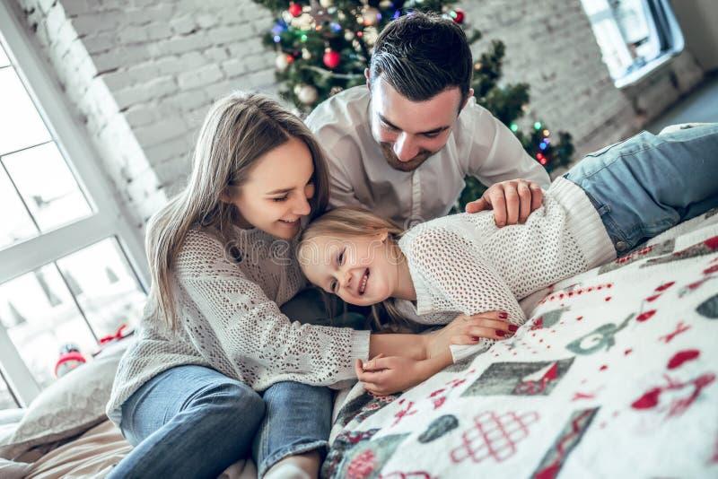 Glückliches Familienporträt des Mutter- und Mädchenkindes, das auf angenehmes Bett in festlich verziertem Raum mit Weihnachtsbaum stockbild