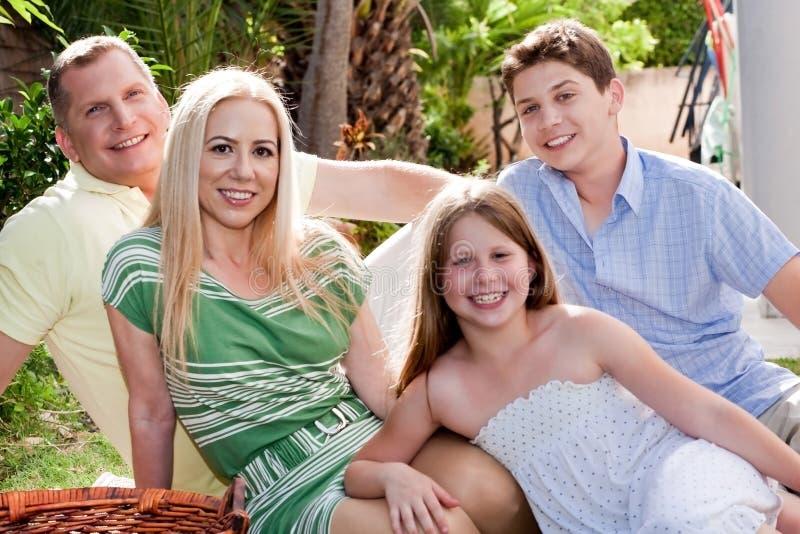 Glückliches Familiensitzen und -ausgabe stockfotografie