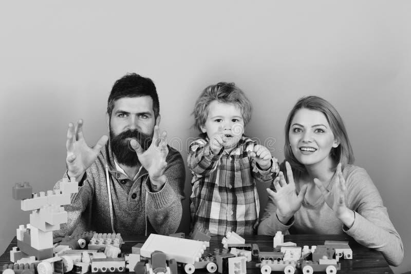 Glückliches Familienspiel Junge Frau und Mann mit dem Kleinkindsohn, der mit Blöcken spielt lizenzfreie stockfotografie