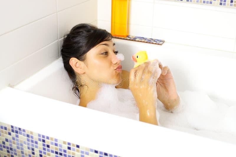 Glückliches Frauengenießen und entspannende Badewanne mit gelber Ente lizenzfreie stockfotos