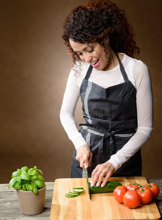 Glückliches Frauenkochen Gesundes Lebensmittel - frische Gurke stockfoto