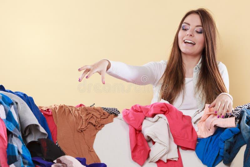 Glückliches Frauensammeln kleidet oben im unordentlichen Raum lizenzfreie stockfotos