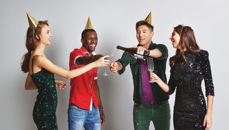 Glückliches Freundtanzen der Unternehmenspartei mit Konfettis und Champagner lizenzfreies stockfoto