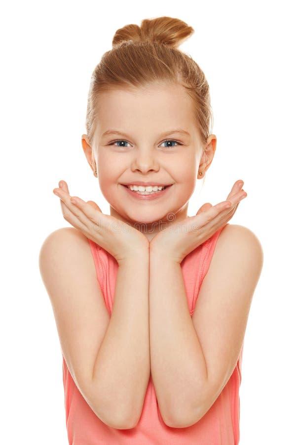 Glückliches frohes kleines Mädchen, das mit den Händen nahe dem Gesicht, lokalisiert auf weißem Hintergrund lächelt stockbild