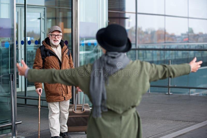 Glückliches gealtertes Paar trifft sich im Ankunftsbereich stockfotografie