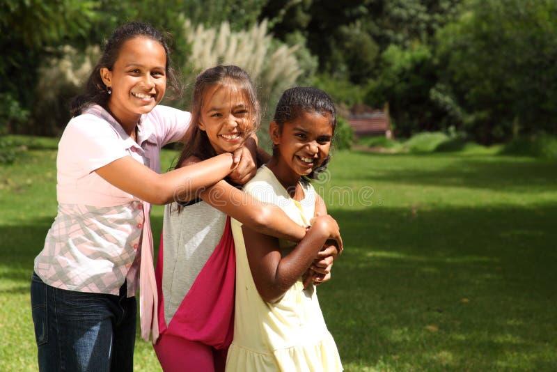 Glückliches Gelächter und Umarmungen von drei Schulefreunden stockfotografie