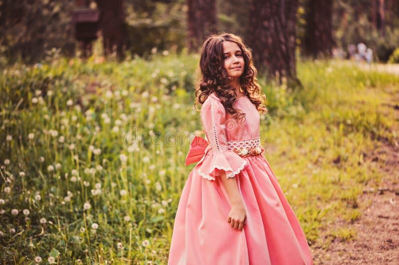 Glückliches gelocktes Kindermädchen im Märchenprinzessinrosa-Kleidertanzen im Sommerwald lizenzfreies stockbild