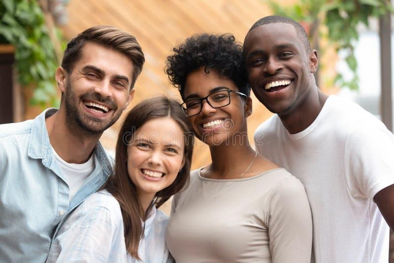 Glückliches gemischtrassiges Freundgruppenabbinden, das Kamera, Porträt betrachtet lizenzfreie stockbilder