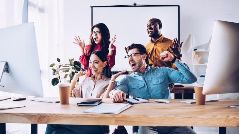 glückliches gemischtrassiges Geschäftsteam, das zusammen an Projekt arbeitet lizenzfreie stockfotos