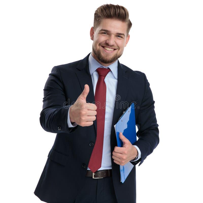 Glückliches Geschäftsmanngestikulieren okay und Halten eines Notizblockes stockfoto