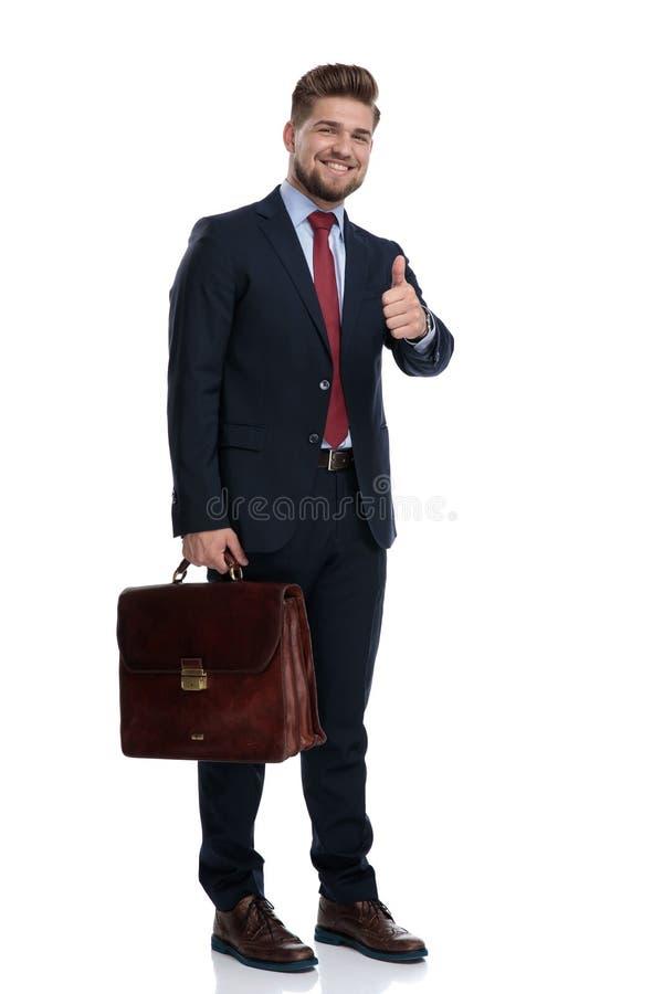 Glückliches Geschäftsmanngestikulieren okay und Halten seines Aktenkoffers lizenzfreies stockbild