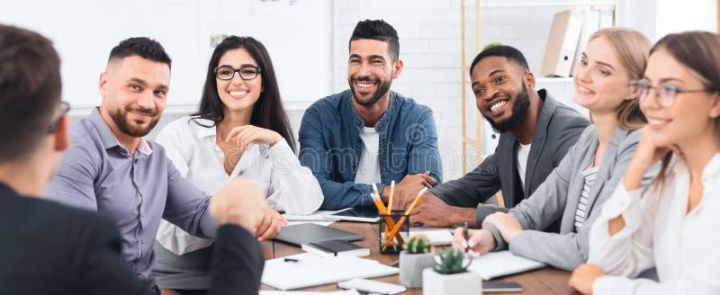 Glückliches Geschäftsteam, das auf Direktor am Treffen hört stockbilder