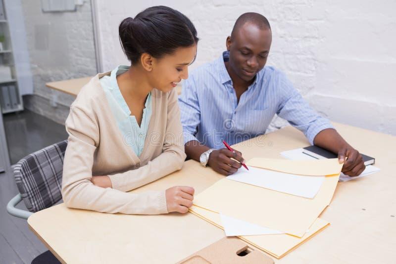 Glückliches Geschäftsteam, das am Schreibtisch zusammenarbeitet lizenzfreies stockbild
