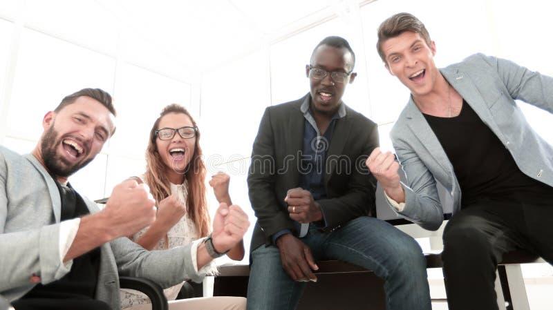 glückliches Geschäftsteam an dem Arbeitsplatz lizenzfreie stockbilder