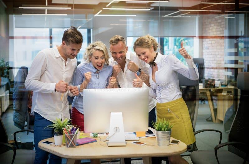 Glückliches Geschäftsteam feiern Erfolg bei der Arbeit stockbild