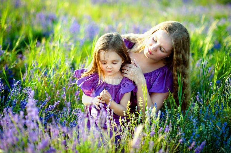 Glückliches gesundes Familienkonzept Eine junge Schönheit mit ihrer kleinen netten Tochter, die auf dem Weizengoldgebiet auf a ge lizenzfreies stockfoto