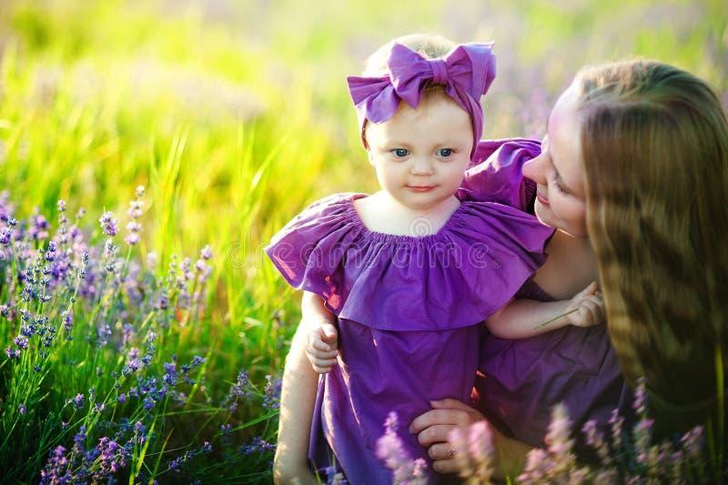 Glückliches gesundes Familienkonzept Eine junge Schönheit mit ihrer kleinen netten Tochter, die auf dem Weizengoldgebiet auf a ge lizenzfreie stockfotos