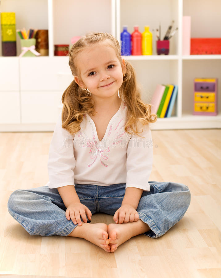 Glückliches gesundes kleines Mädchen, das auf dem Fußboden sitzt stockfotos