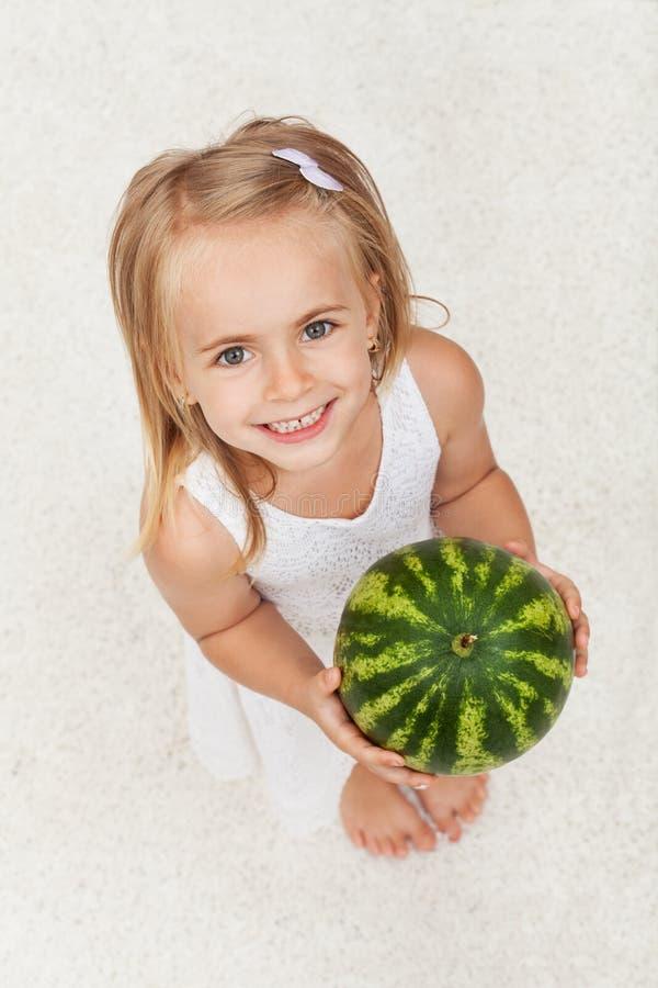 Glückliches gesundes kleines Mädchen, das eine Wassermelone - oben schauend hält stockfotografie
