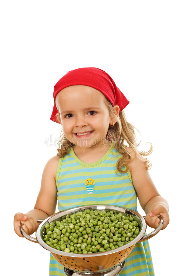 Glückliches gesundes kleines Mädchen mit frischen Erbsen lizenzfreie stockfotografie