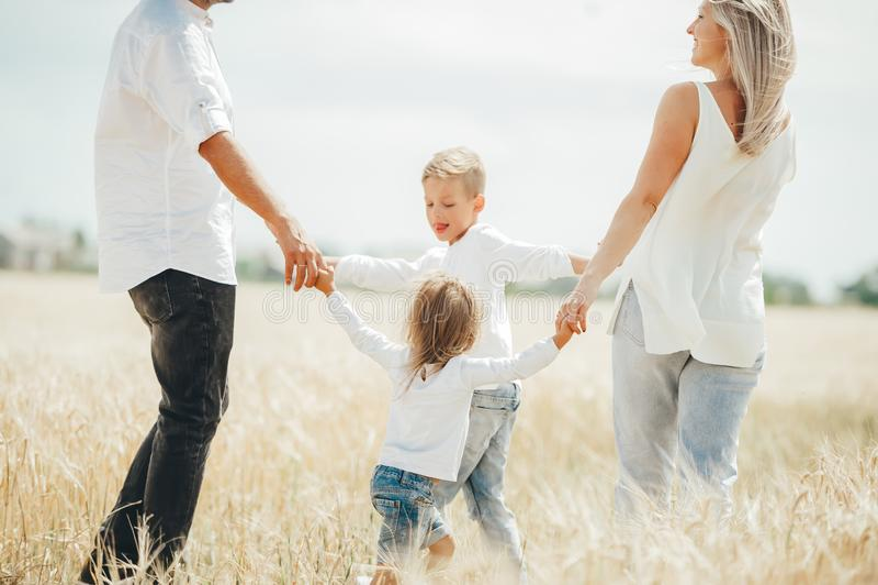 Glückliches Händchenhalten der vierköpfigen Familie, das in Kreis auf einem Weizenfeld tanzt stockfoto