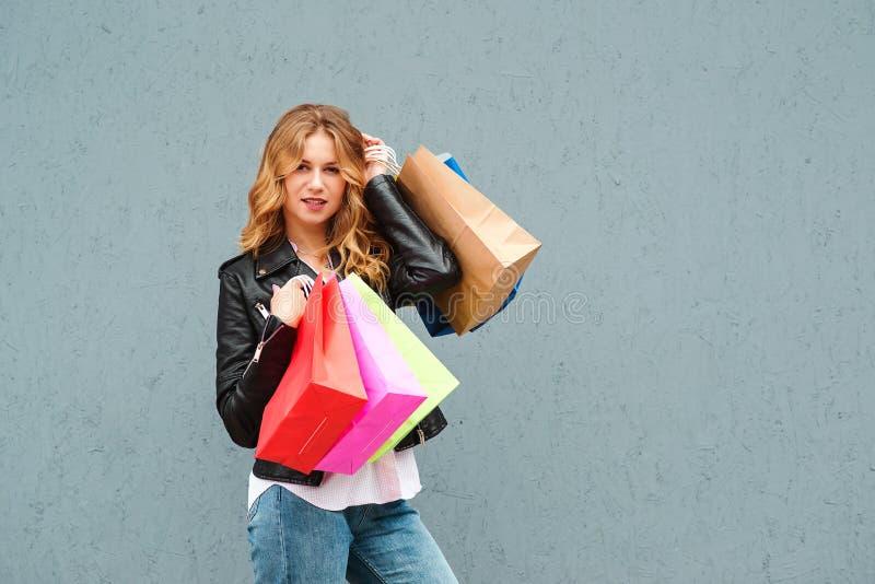 Glückliches hübsches Mädchen, das Einkaufstaschen über grauem Hintergrund hält Verbraucherschutzbewegungs-, Einkaufs-, Verkaufs-  lizenzfreies stockbild