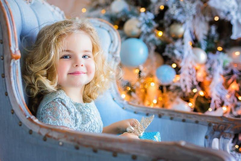 Glückliches hübsches Mädchen, das im Stuhl sitzt und Weihnachtsgeschenk hält lizenzfreies stockfoto