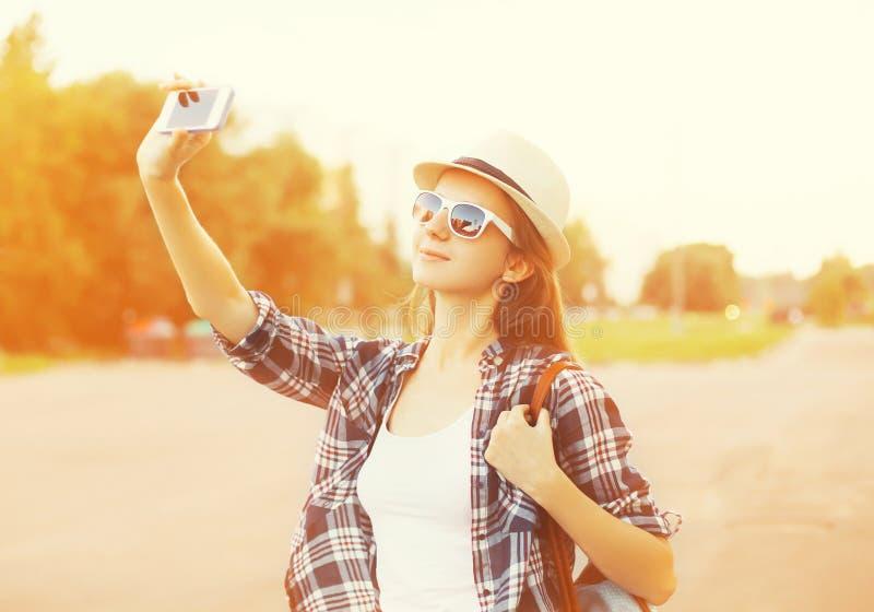 Glückliches hübsches Mädchen macht Selbstporträt auf dem Smartphone lizenzfreie stockfotografie