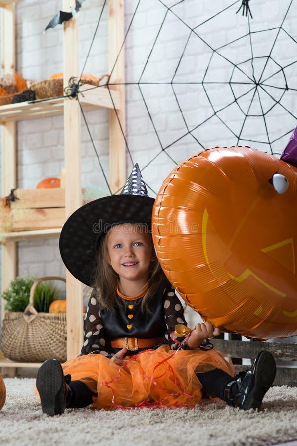 Glückliches Halloween Ein kleines schönes Mädchen in einem Hexenkostüm cele lizenzfreie stockbilder