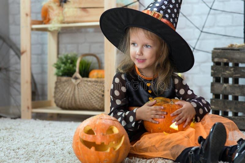 Glückliches Halloween Ein kleines schönes Mädchen in einem Hexenkostüm cele stockfotografie