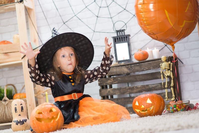 Glückliches Halloween Ein kleines schönes Mädchen in einem Hexenkostüm cele stockbilder