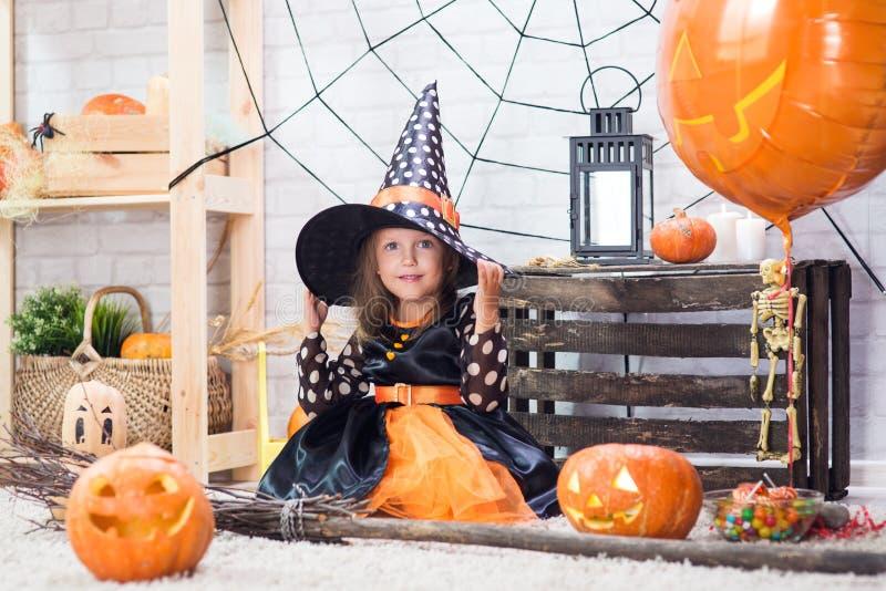 Glückliches Halloween Ein kleines schönes Mädchen in einem Hexenkostüm cele lizenzfreie stockfotos