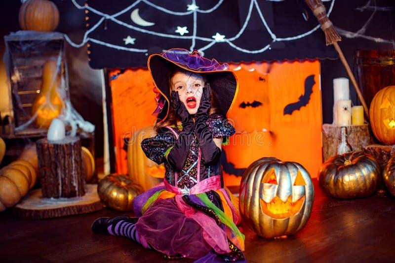 Glückliches Halloween Ein kleines schönes Mädchen in einem Hexenkostüm feiert mit Kürbisen stockfoto