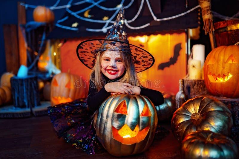 Glückliches Halloween Ein kleines schönes Mädchen in einem Hexenkostüm feiert mit Kürbisen stockfotos